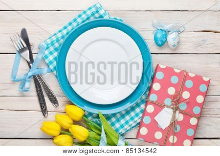 Easter with yellow tulips, colorful eggs and gift box. Top view