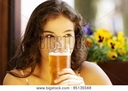 Portrait of a woman drinking beer in bar.