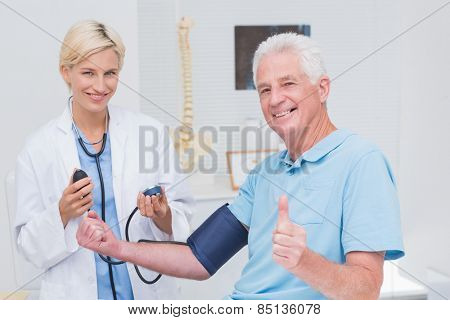 Portrait of happy patient showing thumbs up while doctor checking his blood pressure in clinic