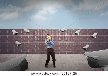 Geeky hipster biting his nails against blue sky over a brick wall