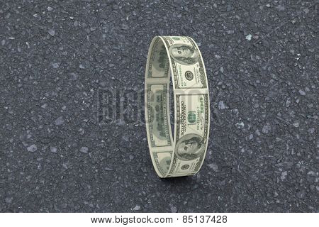 Wheel of dollars against road