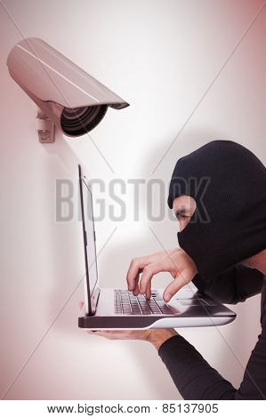 Focused burglar with balaclava typing on laptop against cctv camera