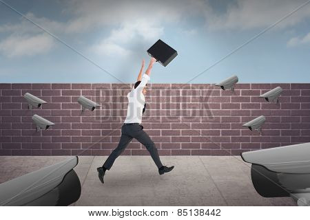 Businessman leaping with his briefcase against blue sky over a brick wall