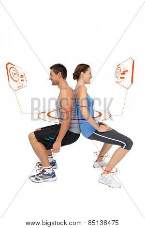 Side view of a fit young couple doing squats against fitness interface