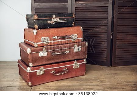 Old suitcases on a background of dark wood screen