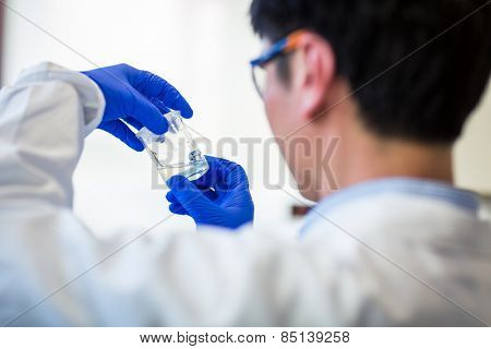 Male researcher carrying out research in a chemistry lab (color toned image; shallow DOF)