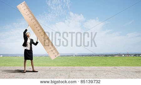 Young businesswoman measuring something with big ruler