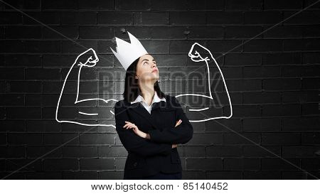 Pretty businesswoman with crown on head representing power