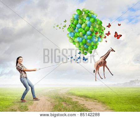 Young woman in casual and giraffe on lead