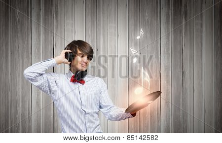 Young man dj wearing headphones and holding plate