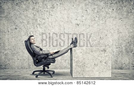 Young confident businessman sitting in chair with book in hands