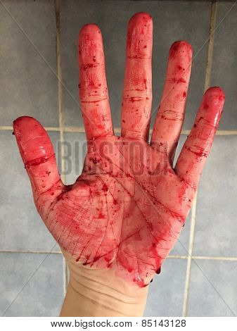 Open female fist covered in blood against the gray tiles