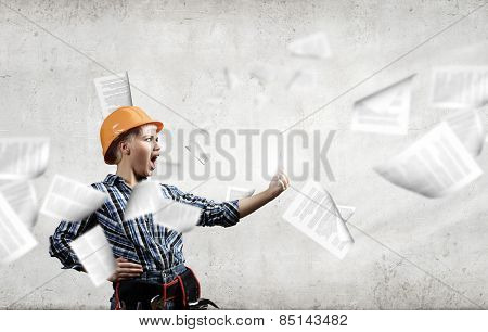 Young woman builder screaming emotionally in mobile phone