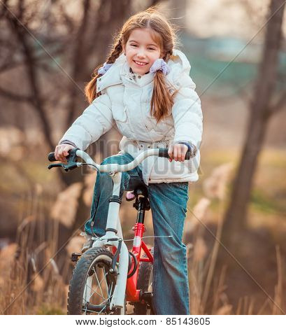 Happy cute little girl on a bicycle in the spring