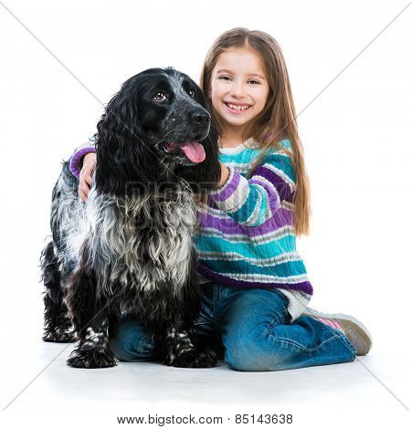 Happy little girl with her cocker spaniel puppy dog isolated on a white background