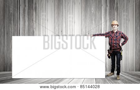 Young smiling craftsman holding with blank banner. Place for text