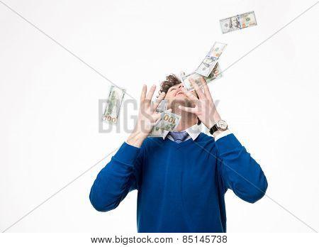 Happy businessman raising hands up and looking up under money rain