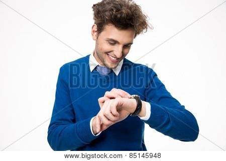 Happy businessman looking at watch over white background