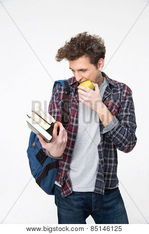 Happy young man looking at the book and biting apple