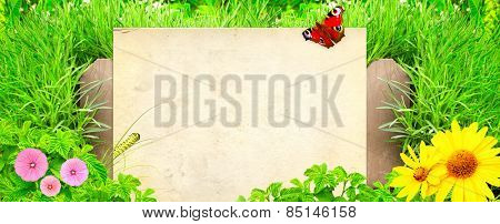 Summer background with paper, old wooden fence and green grass