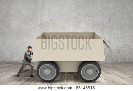 Young businessman pushing carton box on wheels