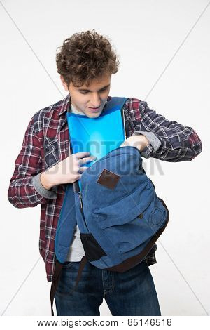 Male student pulls out of a backpack something over gray background