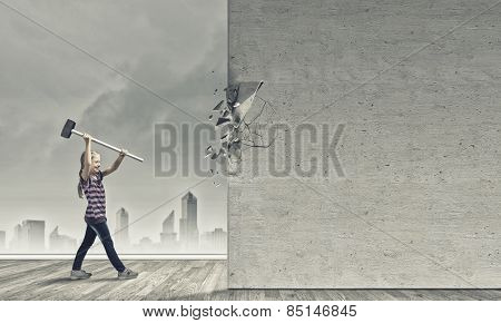 Cute little girl crushing cement wall with hammer