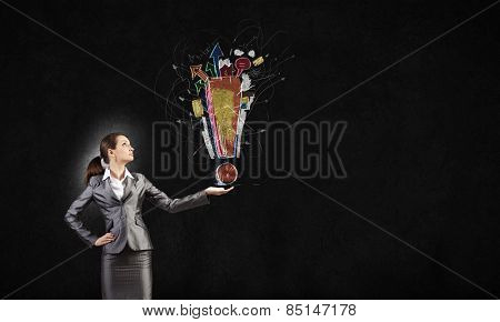 Young businesswoman holding exclamation mark in palm