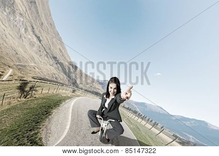 Young pretty businesswoman riding three wheeled bike