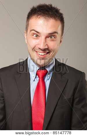 Young business man making a hilarious face, on grey studio background.