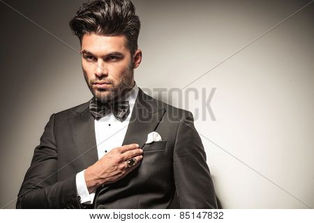 Close up picture of a handsome young business man looking away from the camera while fixing his collar.