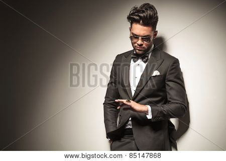 Elegant young business man holding one hand in his pocket while looking down at his golden ring.