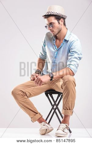 Side view of a casual fashion man sitting on a stool while looking down.