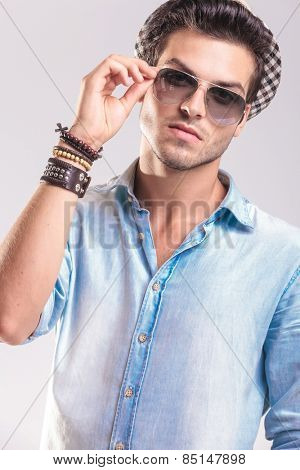 Casual fashion man looking at the camera while taking off his sunglasses, on studio backgroud.