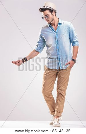 Full body picture of a fashion man looking down while snappig his fingers, on grey studio background.