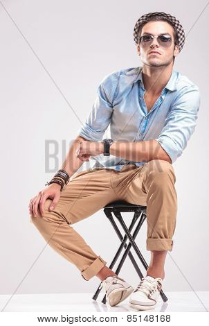 Cute fashion man sitting on a stool while looking up, rsting his hands on his knee.
