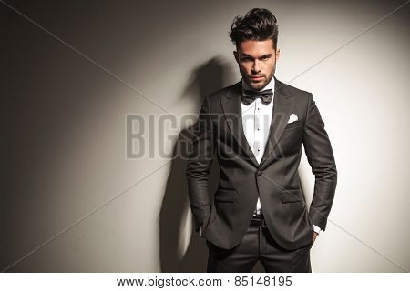 Attractive young business man looking at the camera while holding both hands in his pockets.