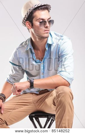 Attractive fashion man resting on a stool while looking to his side, holding his hand on his knee.