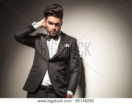Handsome business man scratching his head while looking away from the camera, holding one hand in his pocket.
