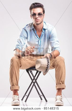Casual fashion man sitting on a stool, holding his hat in his left hand while looking at the camera.