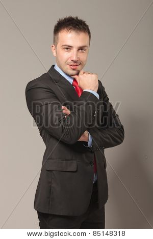 Side view picture of a young business man posing with his arms crossed while holding his thumb to his chin.