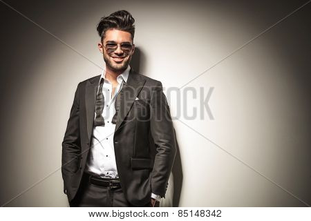 Attractive young elegant business man smiling while holding both hands in his pocket.
