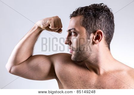 Portrait of muscular man pulling his bicep to show off
