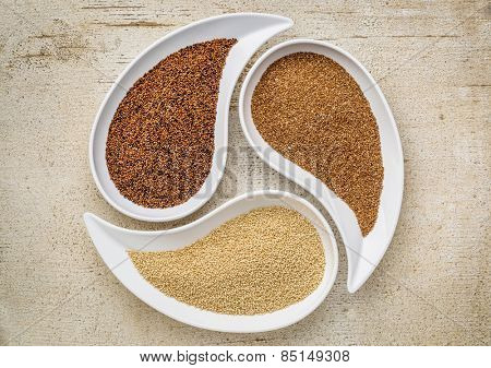 three tiny gluten free grains - kaniwa, amaranth and teff on teardrop shaped bowls against white painted rustic wood
