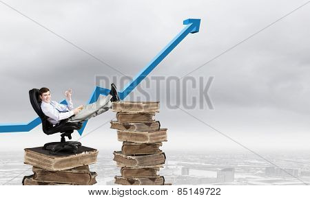 Young businessman sitting in chair with legs on pile of old books