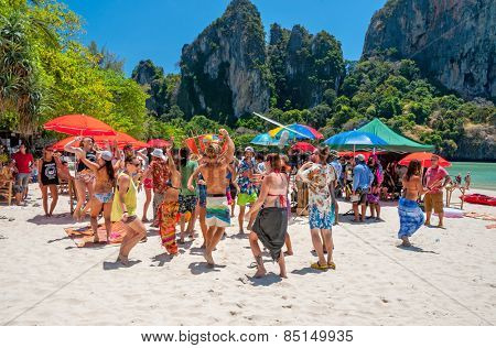 RAILAY, THAILAND - MARCH 13, 2014: Dancing Toutrists while making movie at West Railay beach, one of the most popular rock climbing locations in Asia. on March 13, 2014. Railay, Krabi, Thailand