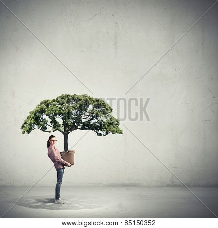 Young girl student carrying big green plant in pot