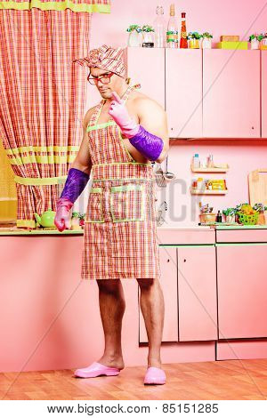 Serious muscular man in an apron standing in the pink kitchen. Love concept. Valentine's day. Women's day.