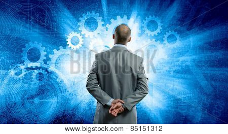Rear view of businessman with arms on head thinking something over