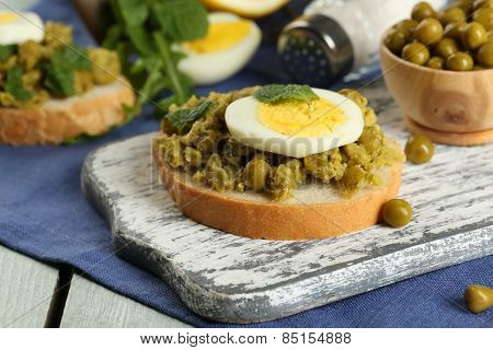 Sandwiches with green peas paste and boiled egg on cutting board with napkin on color wooden planks background